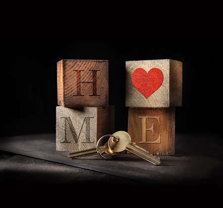Original concept image for loving home purchase. Rustic, creatively lit wooden blocks and golden keys to signify a home purchase with generous accommodation for copy space.