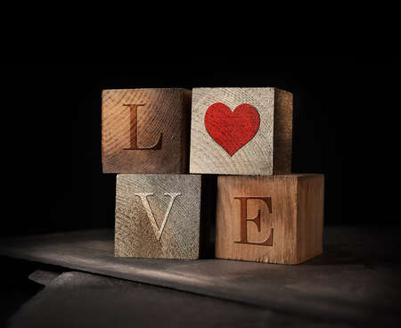 Creatively lit stacked cubes of rustic wooden blocks with the letters LOVE embedded. A concept image for St Valentine's Day. Generous accommodation for copy space if needed.
