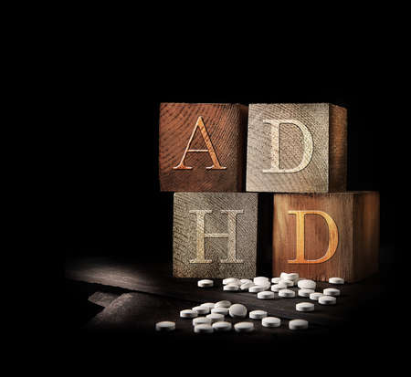 Creatively lit stacked cubes of rustic wooden blocks with the letters ADHD embedded. A concept image for Attention deficit hyperactivity disorder. Generous accommodation for copy space if needed.