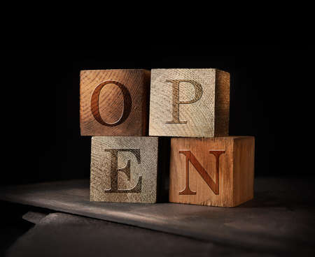 Creatively lit stacked cubes of rustic wooden blocks with the word OPEN embedded. A concept image for Open For Business after COVID-19 lockdowns. Generous accommodation for copy space if needed. Standard-Bild