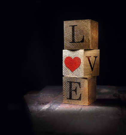 Creatively lit stacked cube squares of real wood with Valentines message of Love, concept image. Generous accommodation for copy space.