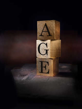 Creatively lit stacked cube squares of real wood with the word AGE embedded shot against a rustic background. Concept image for ageism. Generous accommodation for copy space. Standard-Bild