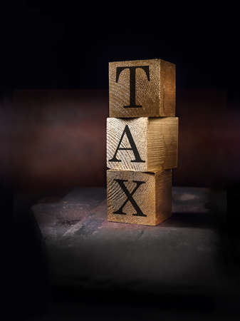 Creatively lit stacked cube squares of real wood with the word tax embedded shot against a rustic background. Concept image for income tax and business. Generous accommodation for copy space.