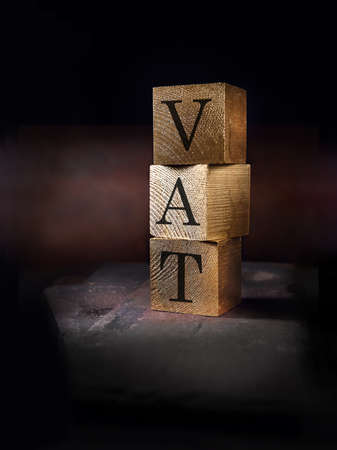 Creatively lit stacked cube squares of real wood with the word VAT embedded shot against a rustic background. Concept image for business finances. Generous accommodation for copy space.