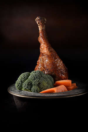 Rustic Roasted Turkey Drumstick with seasonal vegetables of brocolli and carrots, shot against a dark background with generous accommodation for copy space. Standard-Bild