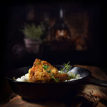 Marinated chicken thighs in coconut milk and then roasted with Moroccan spices served with steamed Basmati rice shot against a dark rustic background. The perfect image for your menu cover art.