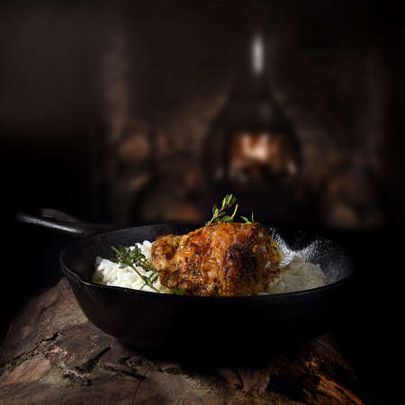 Marinated chicken thighs served with steamed rice shot in a wrought iron, traditional skillet pan, against a dark rustic background. The perfect image for your menu cover art.