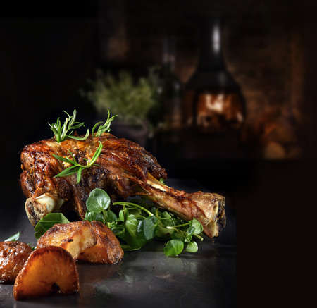 Roasted shoulder of lamb with rosemary, garlic, watercress garnish and roasted potatoes. Shot against a rustic background with generous accommodation for copy space.