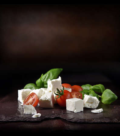 Greek feta cheese with vine tomatoes and basil herb leaves shot against a rustic background with generous accommodation for copy space.