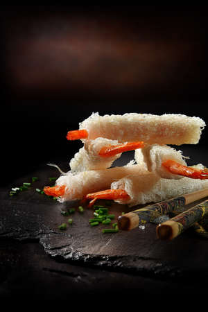 Chinese Prawn Tails In Rice Pastry with fresh chopped chives and chop sticks. Shot against a dark background with generous accommodation for copy space.
