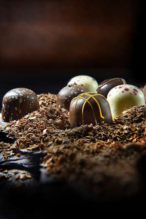 Dark, rustic styled image of liqueur chocolates shot against a dark background with generous accommodation for copy space. The perfect image for your Easter or Valentine's Day cover art.