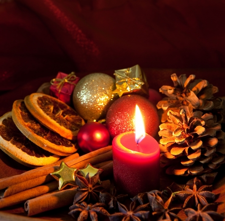 christmas atmosphere: christmas picture with candle, cinnamon sticks, orange and christmas balls Stock Photo