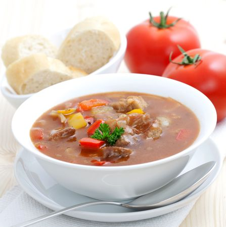 meat soup: fresh goulash with paprika and baguette