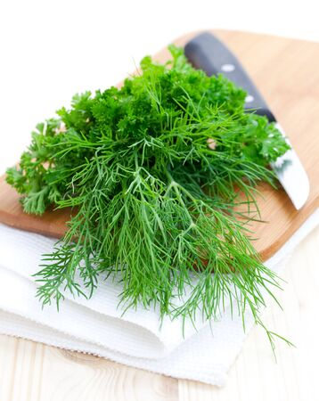 fresh dill and parsley on a cutting board with knife  photo