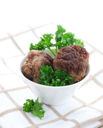 two meat balls in white bowl with parsley  photo