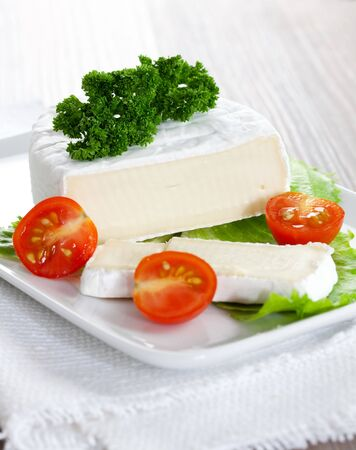 トマトを皿にスライスした柔らかいチーズ
