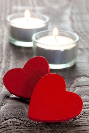 two red hearts with burning candles   photo