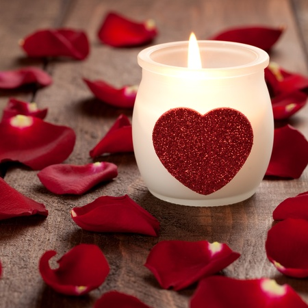 burning candle with heart and rose petals