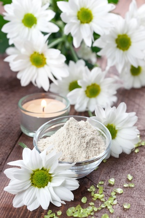aging skin: almond bran in bowl with flowers (spa concept) Stock Photo