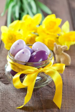 easter eggs in a bowl with ribbon and daffodils photo