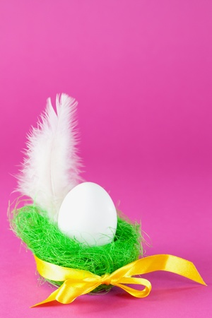 egg in green basket with feather and ribbon  photo