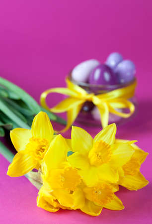 daffodils on pink table with easter eggs in background  photo