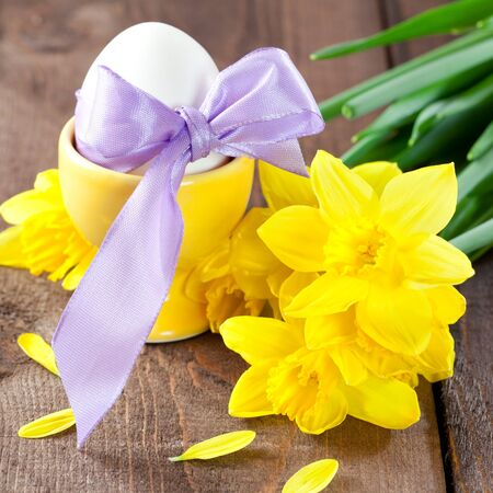 easter egg with ribbon and daffodils on table  photo