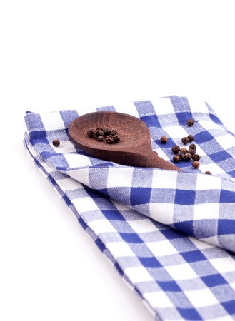 wooden spoon with peppercorn on dishtowel isolated photo
