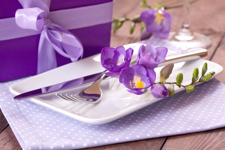 table setting with gift and flowers