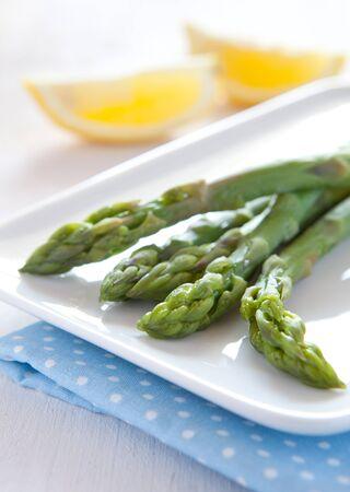 fruit plate: fresh green boiled asparagus and lemon