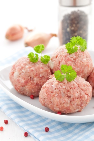 raw meat balls on a plate photo