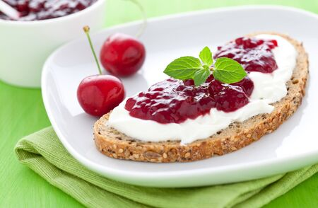 fresh bread with jam with cherries on a plate  Stock Photo