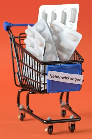 side effect: shopping cart with pills and label side effect german   Stock Photo