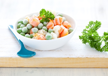 deep freeze: fresh frozen mixed vegetables in bowl with parsley