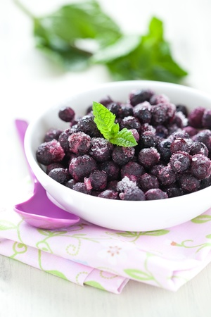 fresh frozen blueberries in bowl with spoon