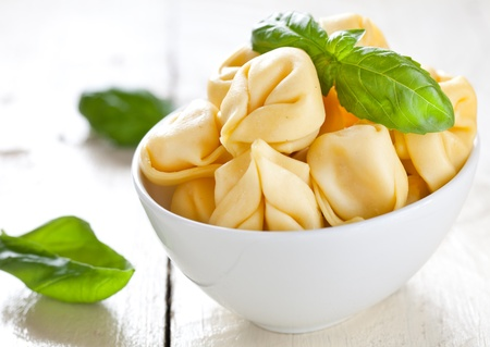fresh tortellini in a bowl with basil  photo