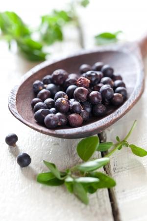 juniper: dried juniper berries on wooden spoon  Stock Photo