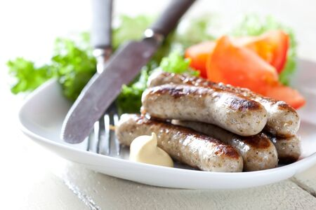grilled sausages: fresh grilled sausages with salad on plate