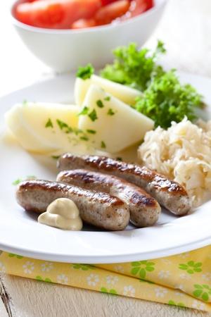 chorizos asados: embutidos frescos de nuremberg con patatas Foto de archivo