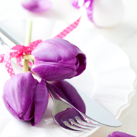 place setting with tulips and cutlery for easter  photo