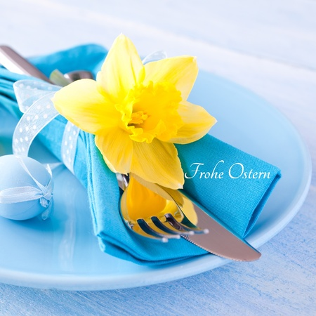 frohe: place setting for easter with cutlery and daffodil german frohe Ostern