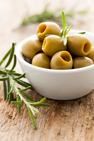 green olives in a bowl with rosemary  photo