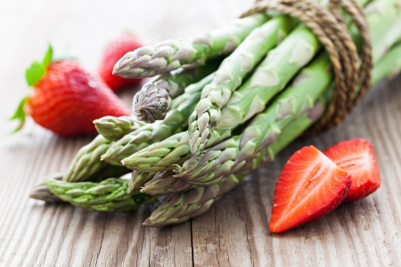 asparagus and strawberries on wood