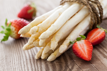 white asparagus and strawberries on wooden table  Standard-Bild