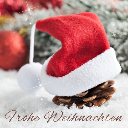 frohe: fir cone with christmas hat and german text frohe weihnachten