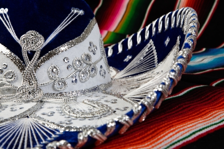 elaborate: Silver and white mexican sombrero with elaborate pattern on a colorful serape blanket