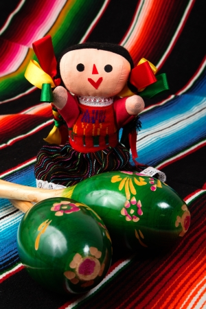 Mexican culture, beautiful traditional doll with maracas on a colorful serape blanket