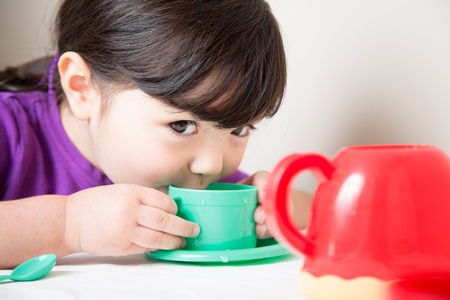 sipping: Young girl sipping from her cup having a tea party