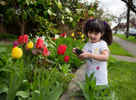 Happy young girl laughing as she captures a photo of spring flowers photo