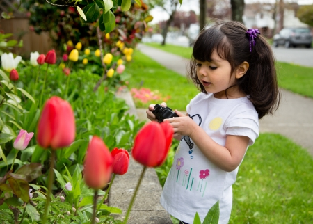 Young photographer reviewing picture of spring flowers on back of camera photo